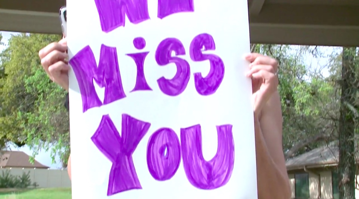 Courtney Leigh holding we miss you sign for residents