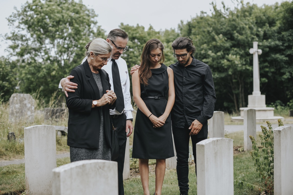 family wearing black to a funeral in a cemetery