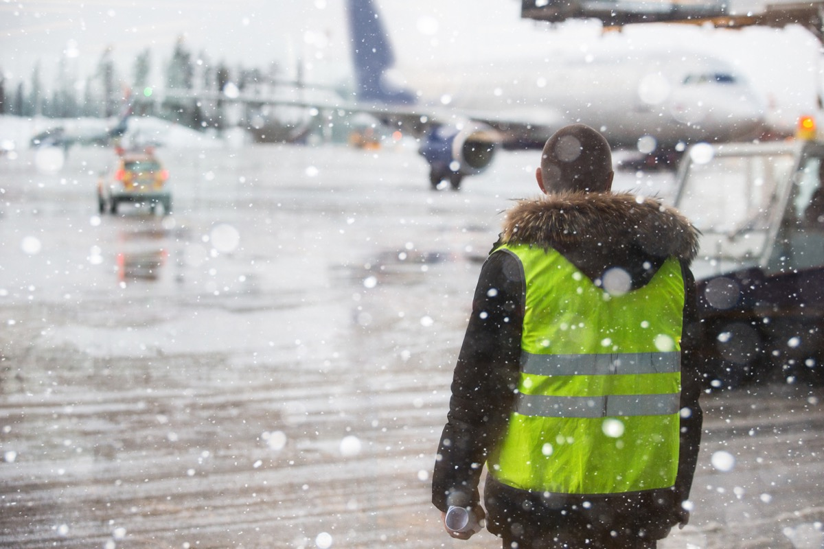 airport ground worker in the middle of a blizzard