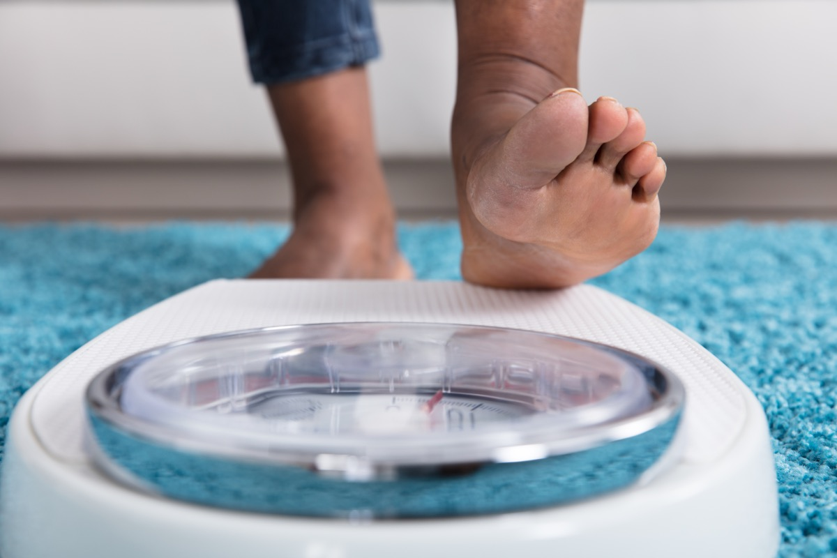 Woman stepping on scale to weigh herself