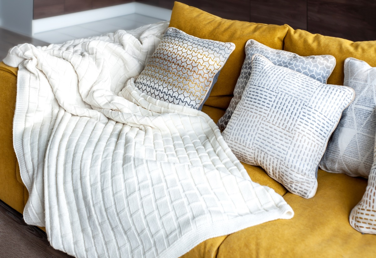 white blanket on yellow couch