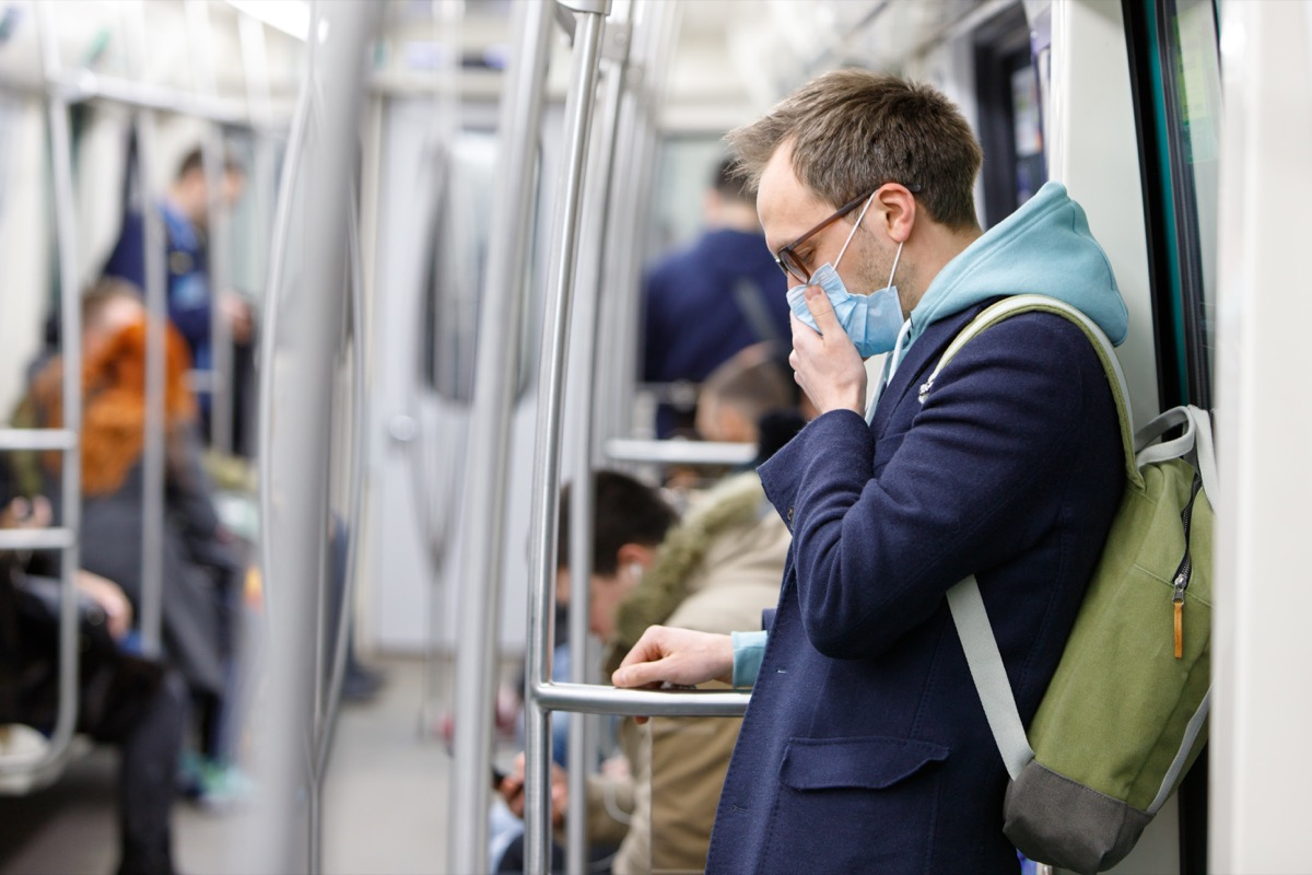white man wearing mask and blue peacoat on subway during coronavirus covid-19 pandemic