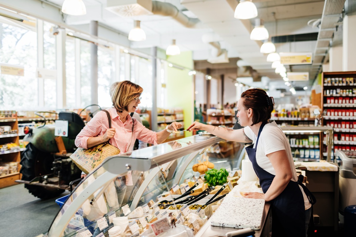 A mature woman tasting a cheese sample at the delicatessen at her local supermarket before making a purchase.