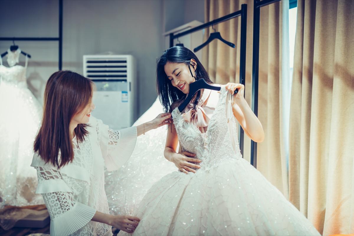 woman choosing a white wedding dress
