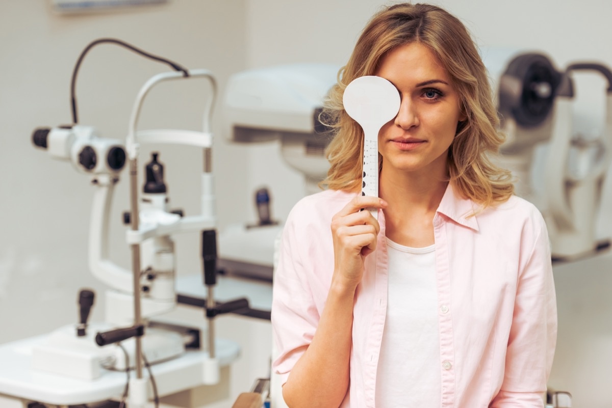 young blonde woman covering one eye at doctor's office