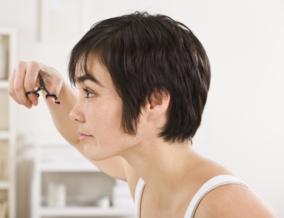 Close-up profile of a woman trimming her bangs. Horizontal shot.