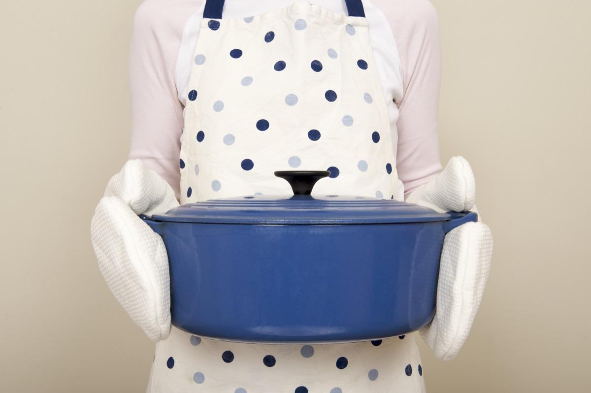 woman holding a blue casserole dish