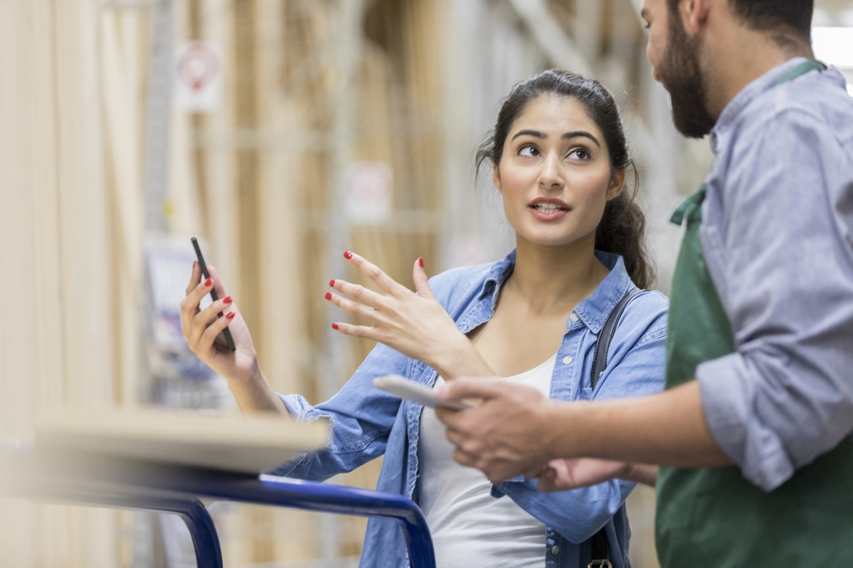 Young woman uses her smart phone to explain her diy project to a hardware store employee