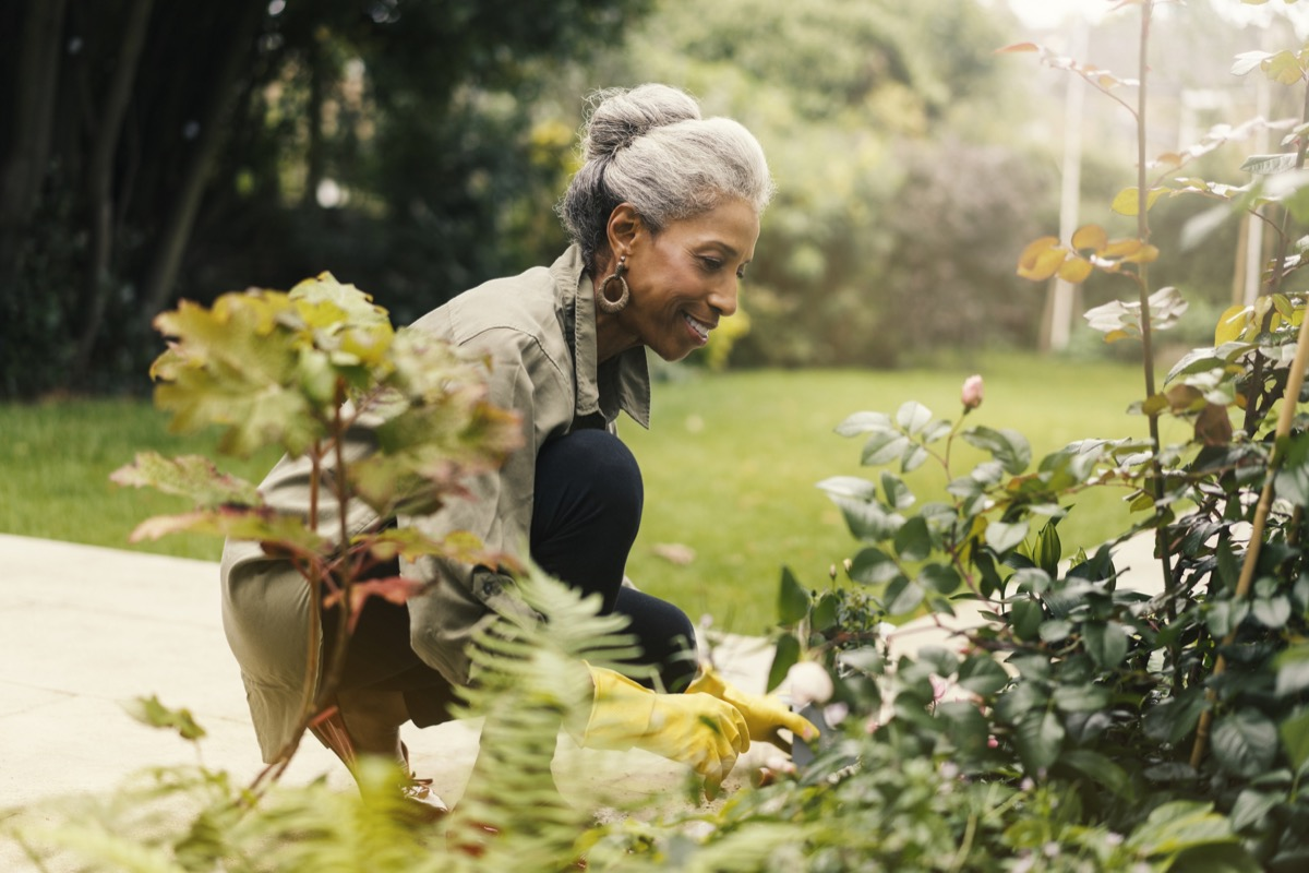 woman crouching and planting her plants in a yard