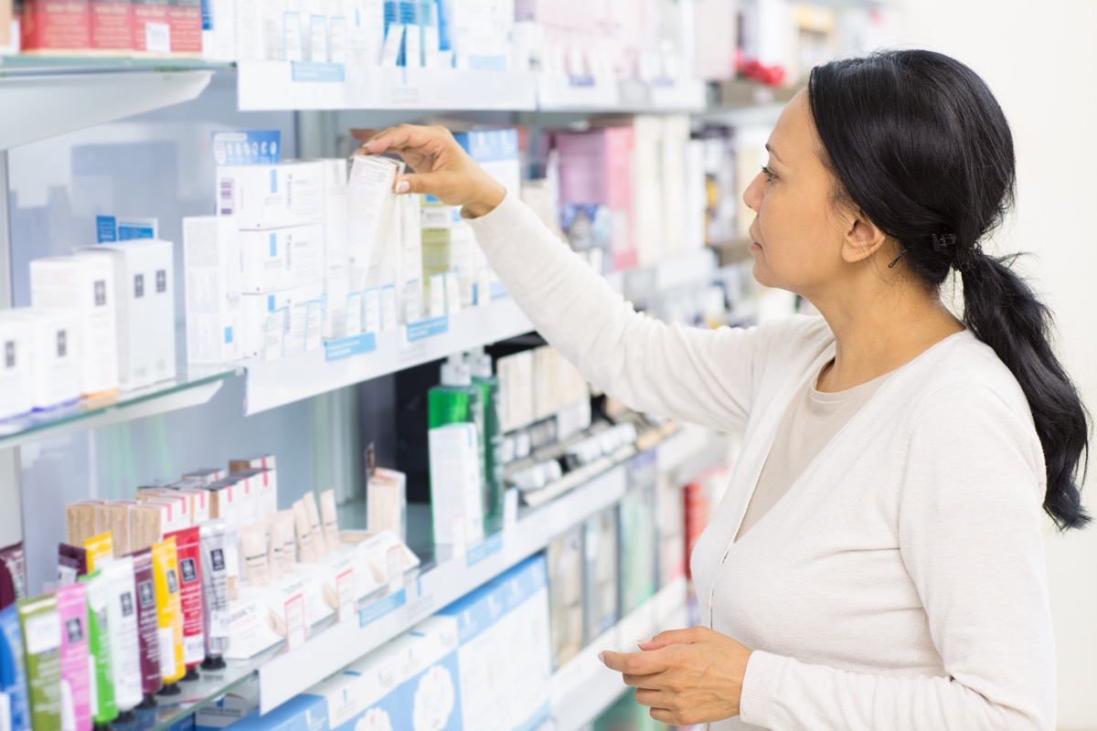 middle aged woman shopping at drugstore or pharmacy