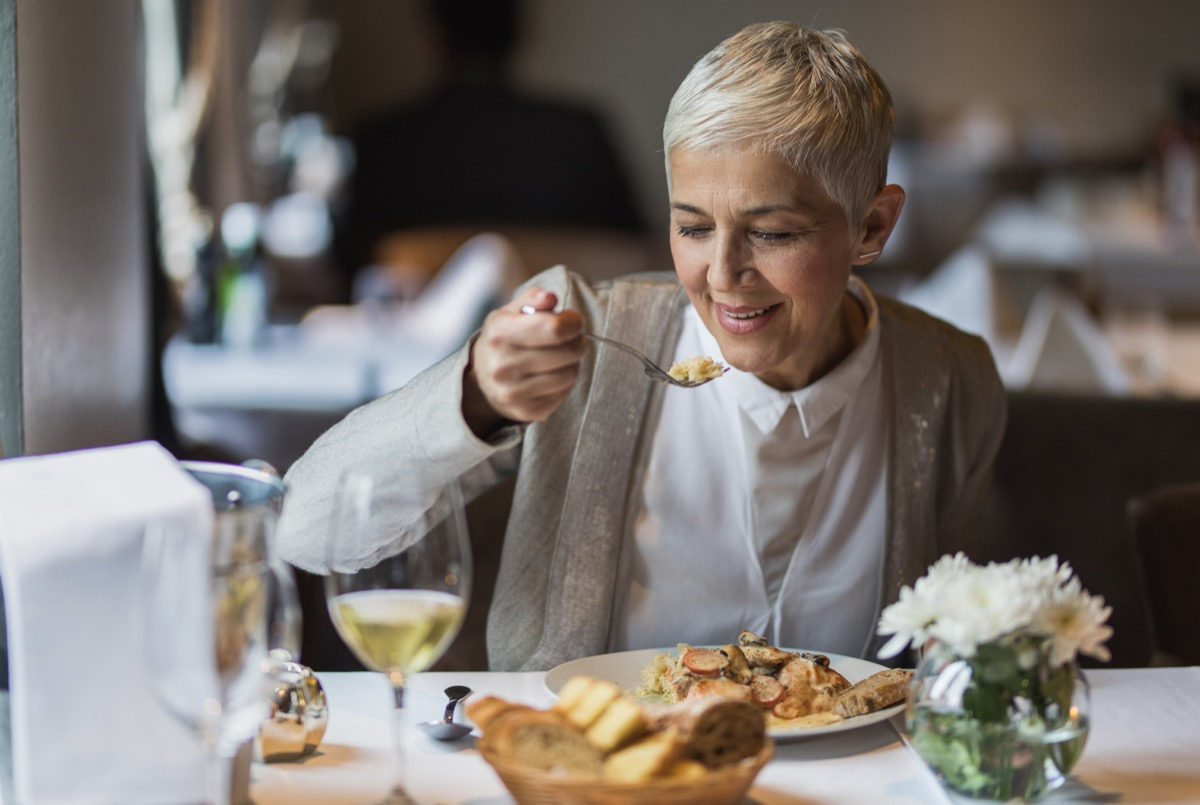 woman sitting with hand in her lap eating dinner