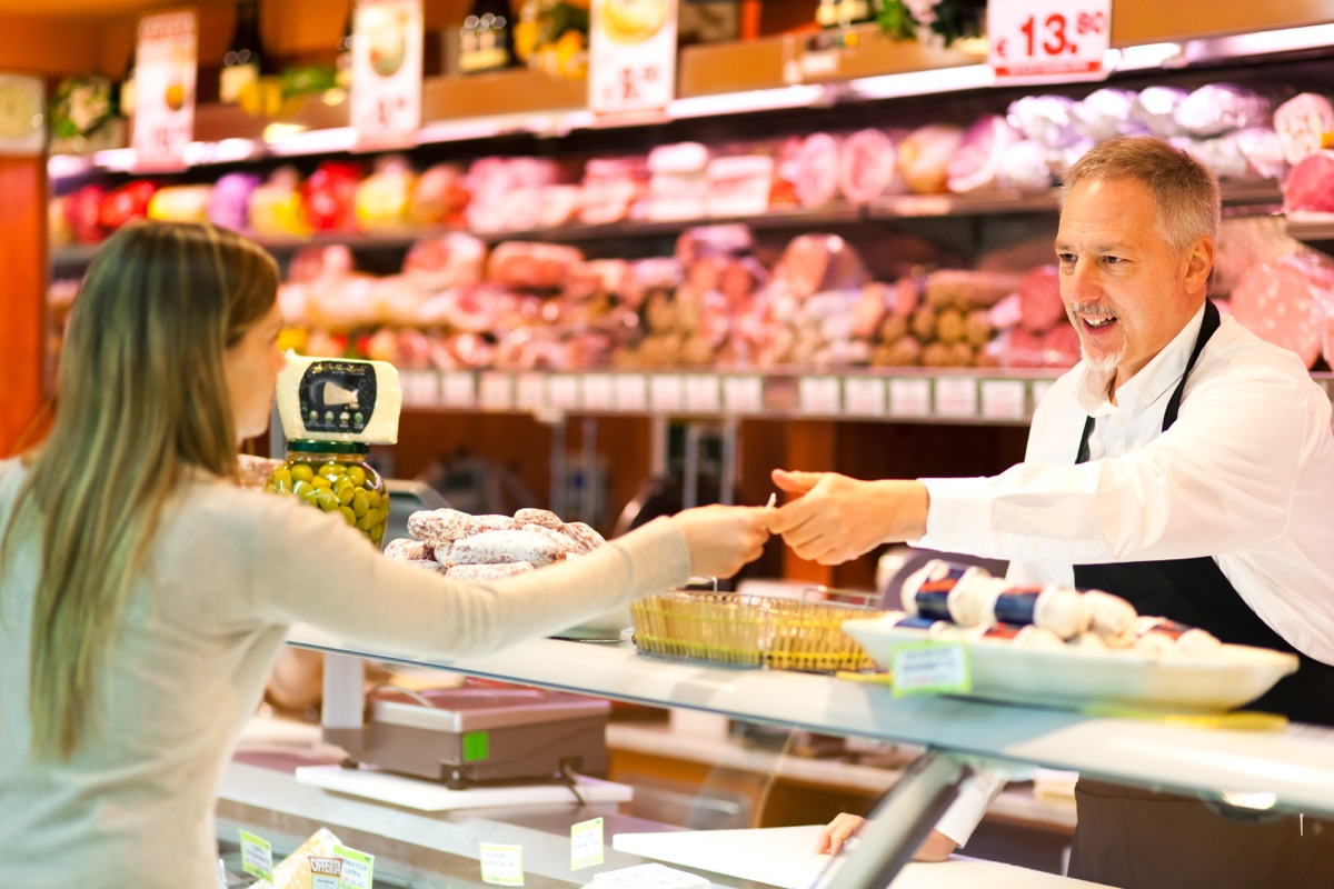 young white woman talking to butcher in grocery store