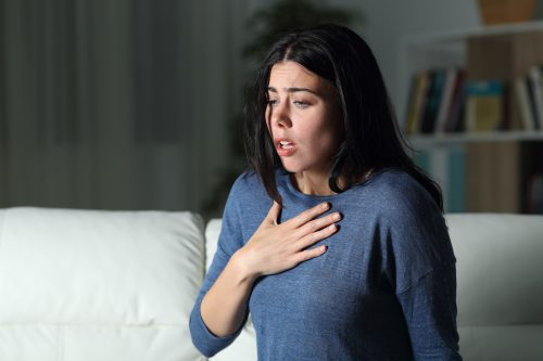 woman alone in house at night has hand on chest as she struggles to breath