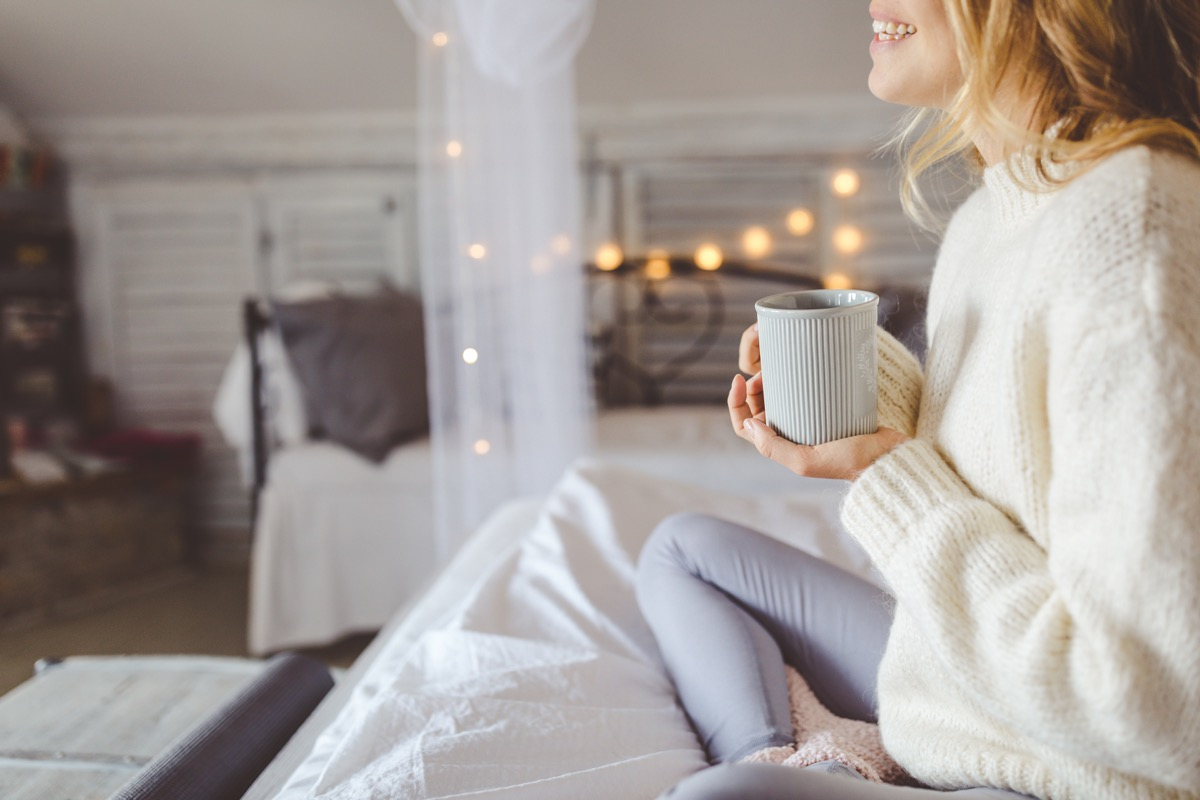 woman wearing white while sitting on her bed drinking a cup of coffee
