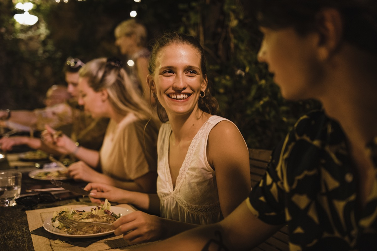 shot of two women talking at a long dinner party table