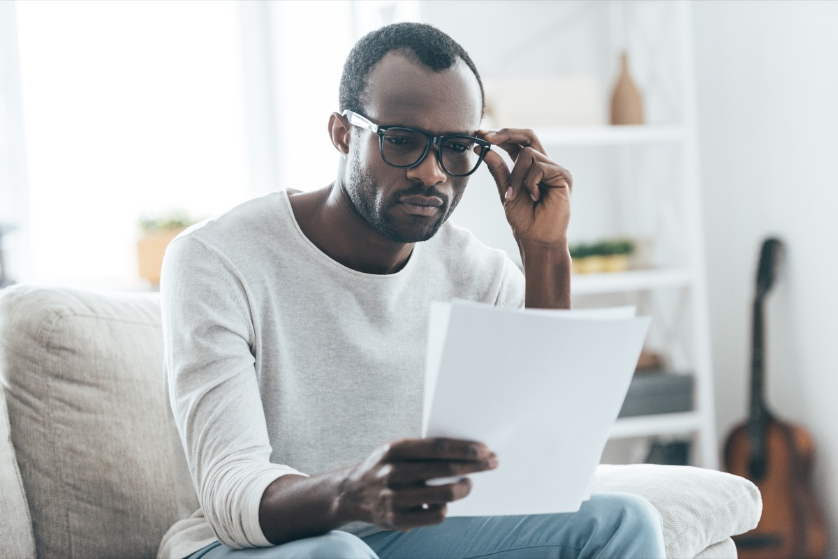 young black man in glasses looking at paper