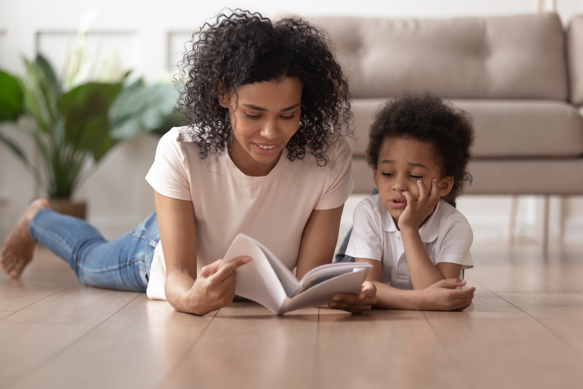 young black mother reading book to son