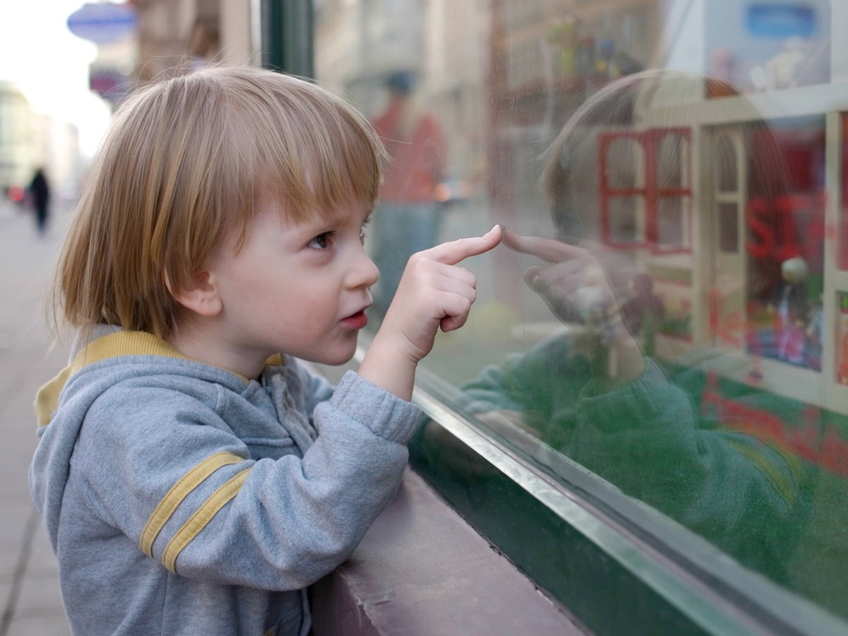 young white boy looking in the window of a toy store