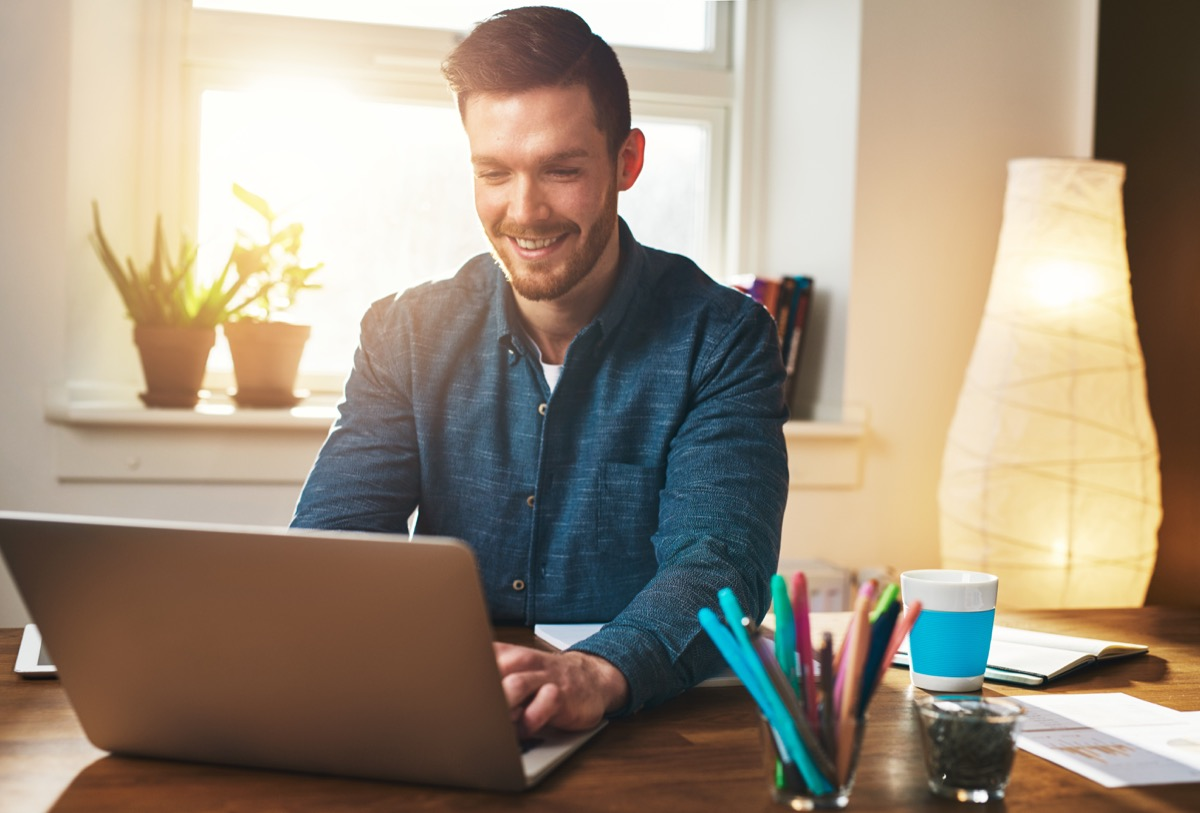 young white man in wfh office working from home in front of window