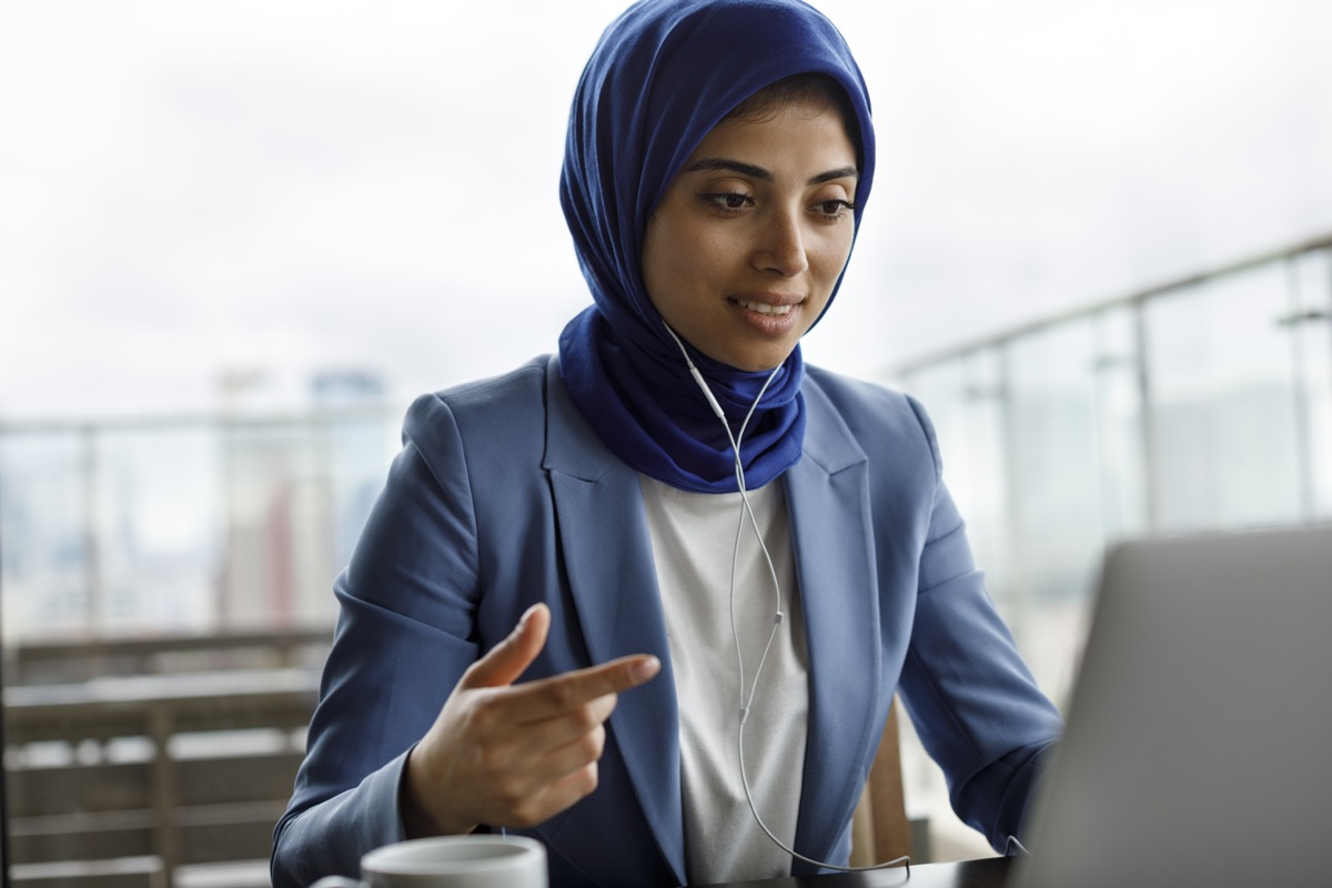 Young woman wearing hijab with headphones working on laptop
