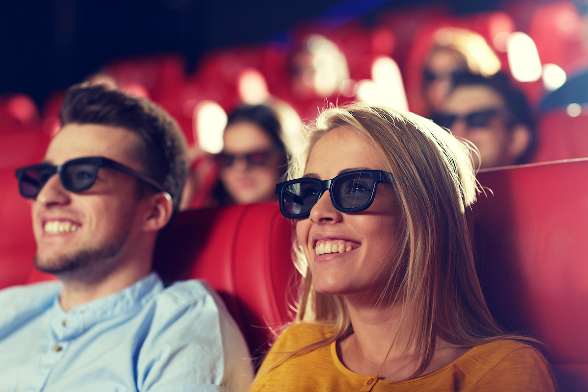 man and woman sit in red movie theater seats in 3D glasses