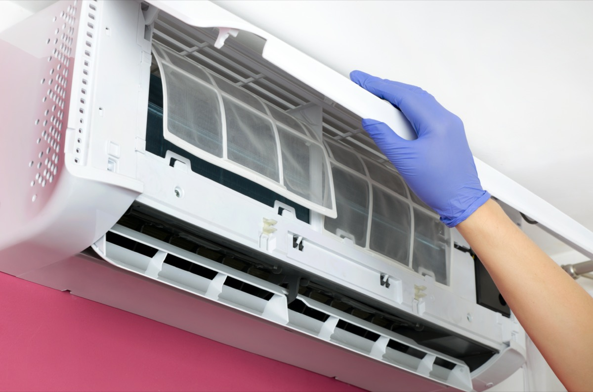 Gloved hand changing an air conditioner filter