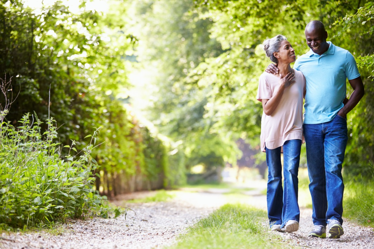 Older black couple walking down path