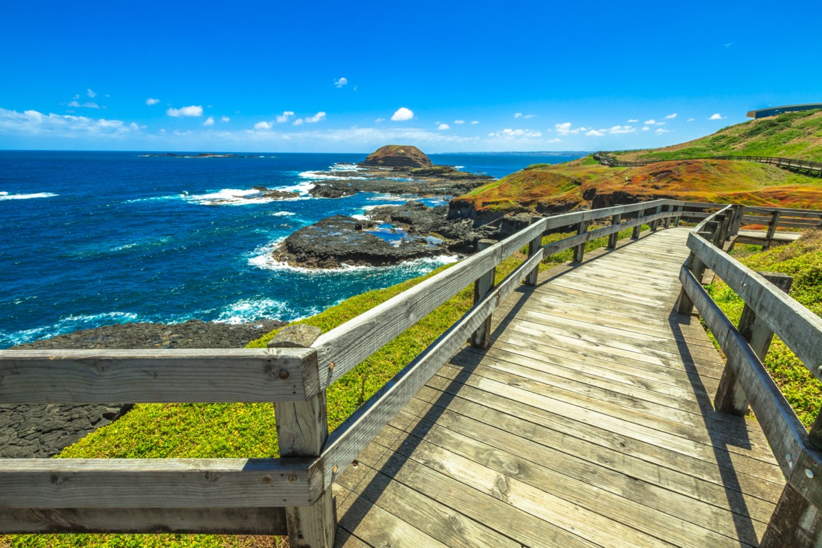 a boardwalk on the side of a coastal cliff overlooking the sea