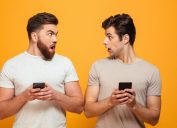 Two men holding phones and looking surprised
