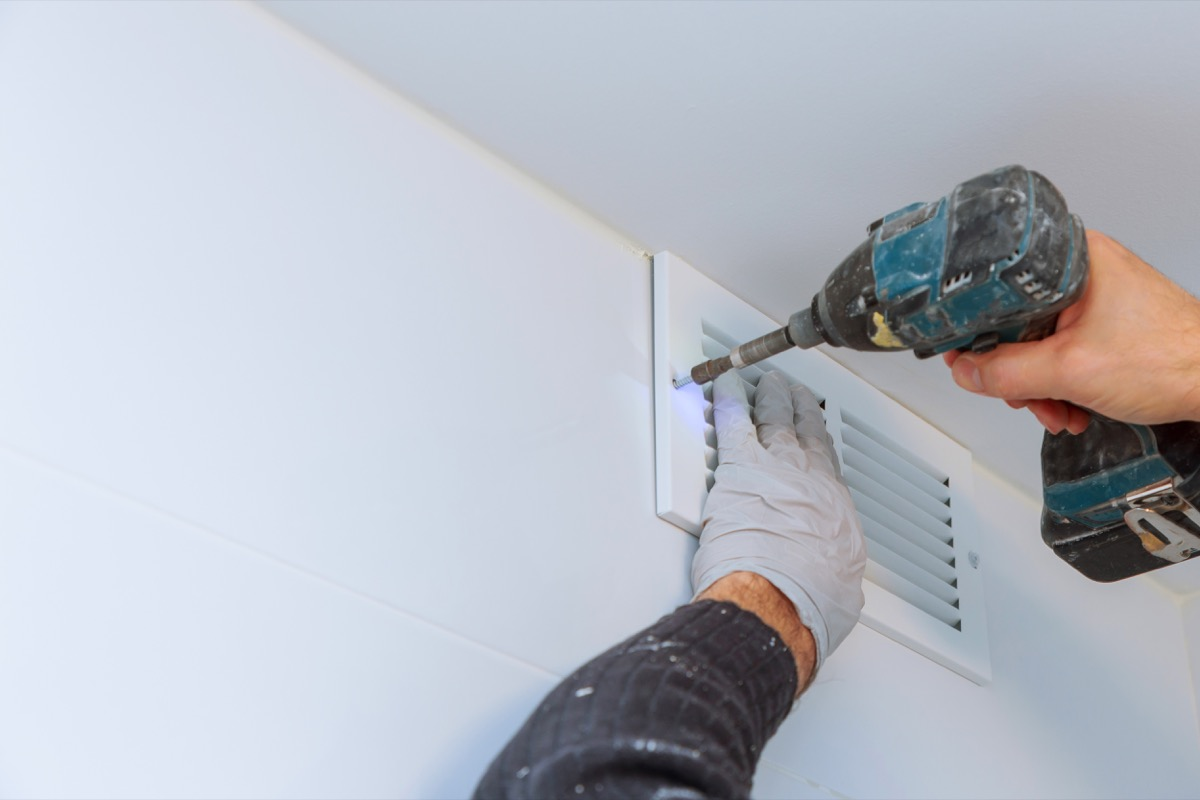 Close up man hand installing vent cover from ceiling Mounted Air Conditioner.