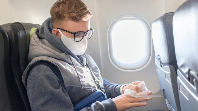 man wears a medical mask and wipes his hands with disinfectant