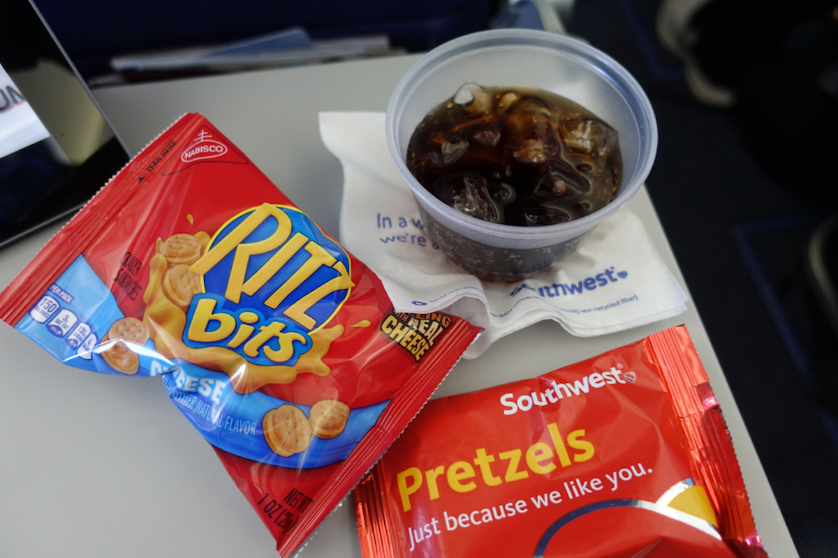 airplane snacks and soda on tray