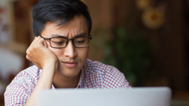 Portrait of bored young male student wearing glasses sitting at laptop leaning on arm