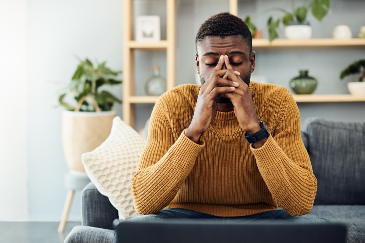 Shot of a young man looking stressed out at home