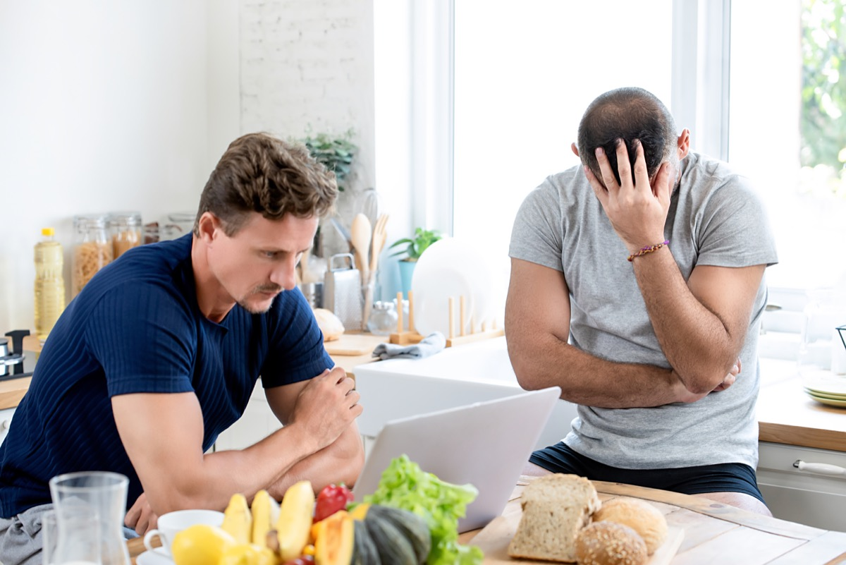 Men having a tense discussion in the kitchen