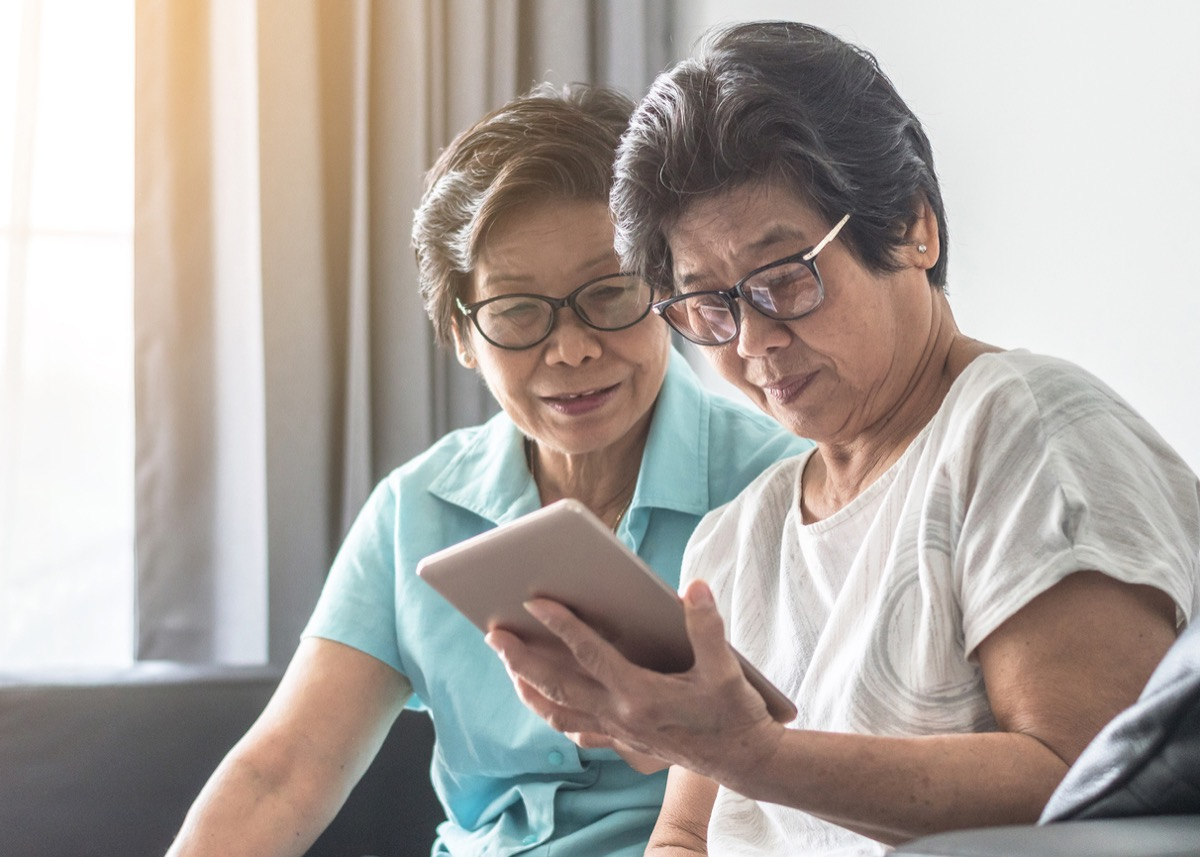 Asian senior adult women who look like twin sisters using mobile digital tablet