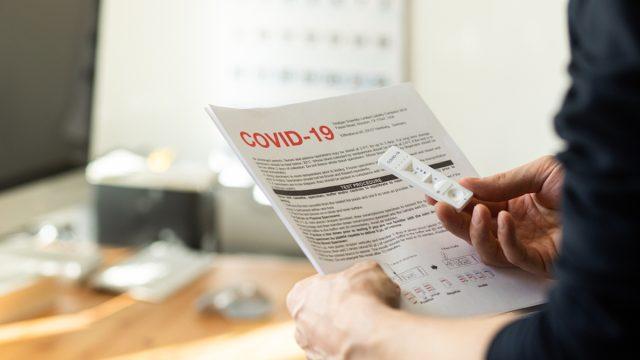 closeup of man's hand doing at-home coronavirus test