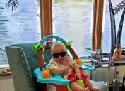 baby with sunglasses on in front of painted windows