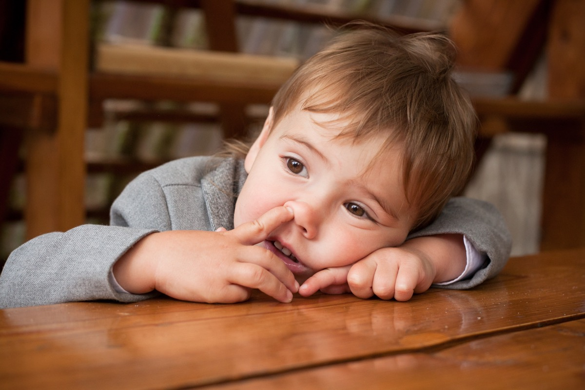 Young child picking nose