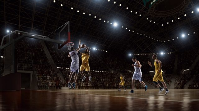 Low angle view of a professional basketball game. A player is in mid air holding ball about to score a slam dunk, but the player from the opposite team is ready to block him. A game is in a indoor floodlit basketball arena. All players are wearing generic unbranded basketball uniform.
