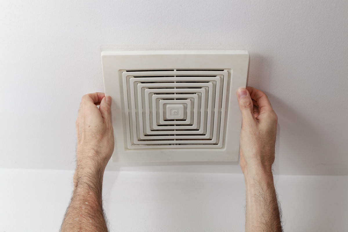 white hands holding bathroom exhaust fan