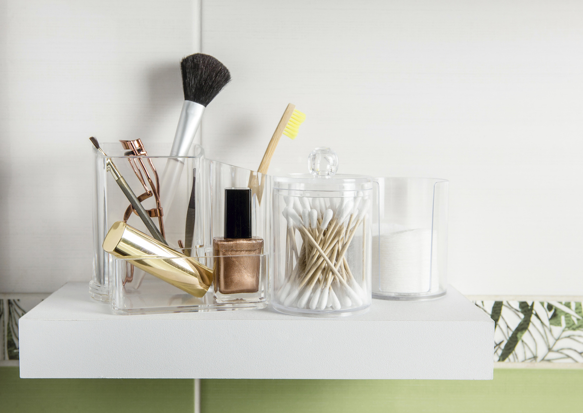 Cotton pads, Q-tips, make up brushes, and more beauty products in organizer container boxes on tidy shelf in bathroom