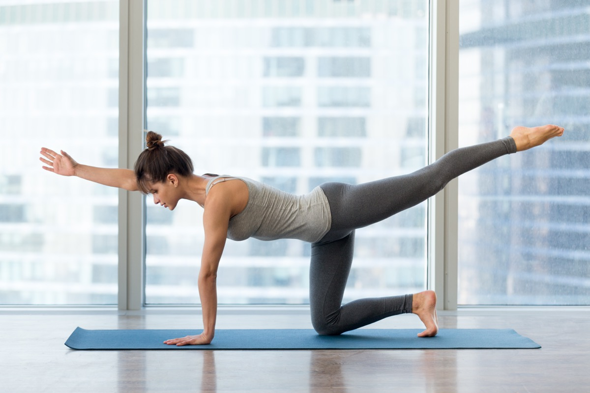 Woman doing bird dog yoga pose