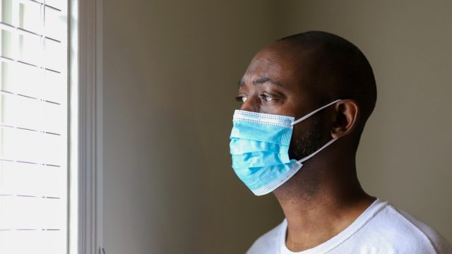 An African-American man wearing a protective face mask to prevent virus infection while staring out window