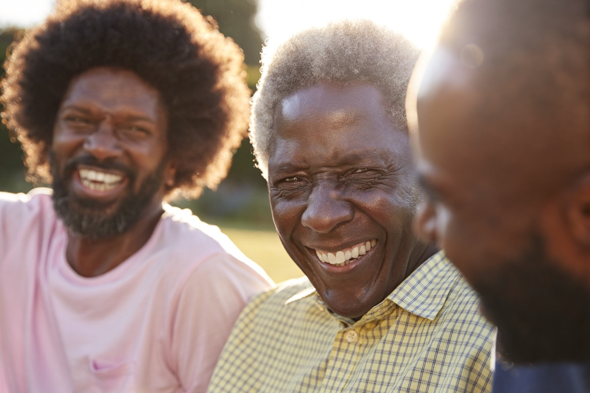 Senior black man laughing with his two adult sons