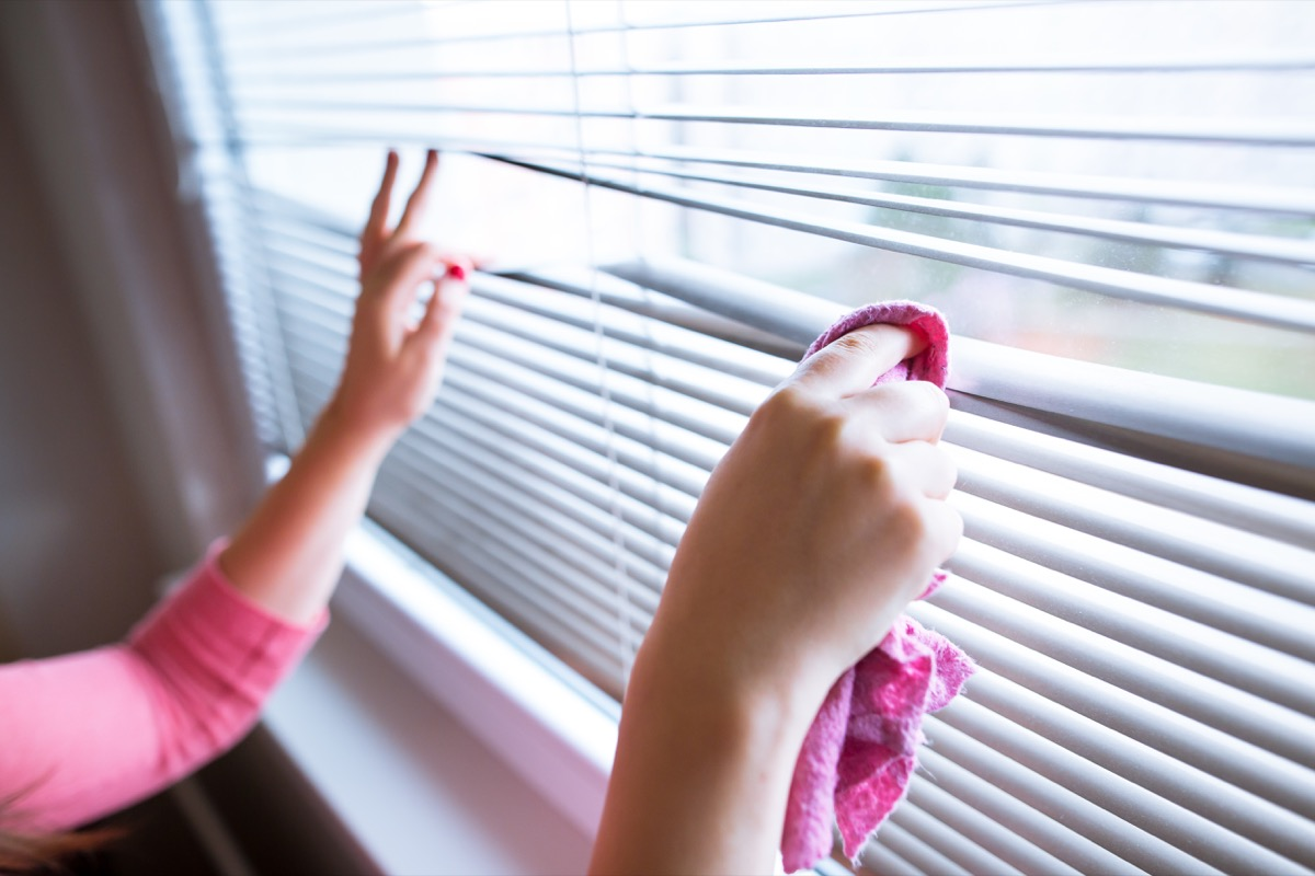 Woman cleaning window blinds