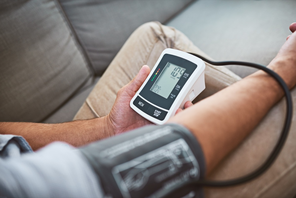 Closeup of an unrecognizable man doing a reading of his blood pressure with a blood pressure monitor while being seated on a couch at home