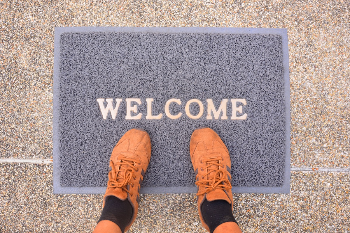 brown sneakers on a gray welcome mat