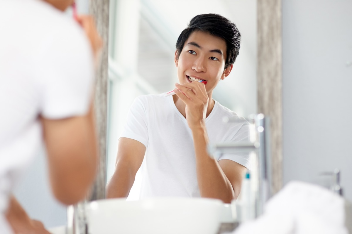 Shot of a handsome young man brushing his teeth in the bathroom at home