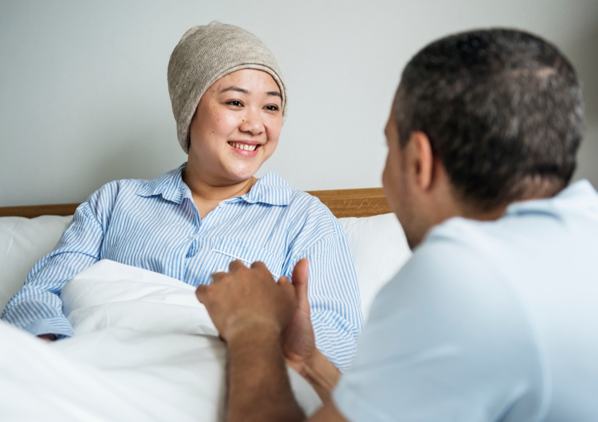 Woman with cancer talking to husband in hospital bed